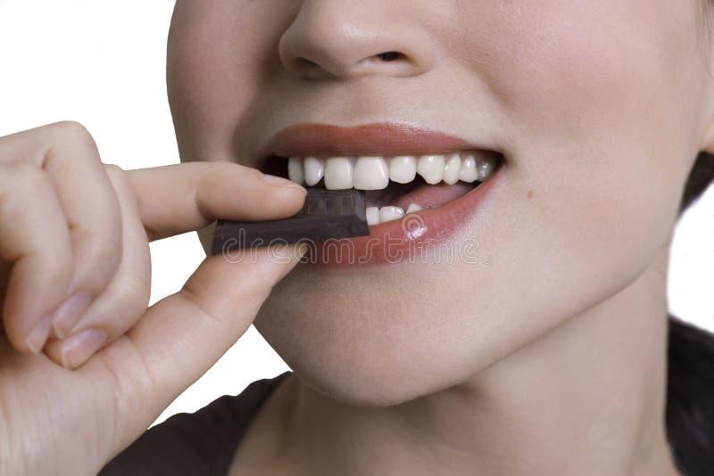 Tir en gros plan de jeune femme mangeant du chocolat amer photographie stock libre de droits