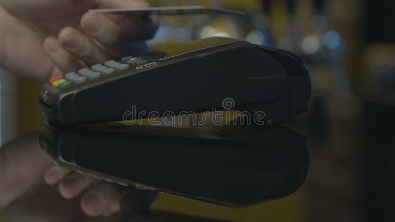 Tir en gros plan de la personne employant le paiement mobile PayPass photographie stock