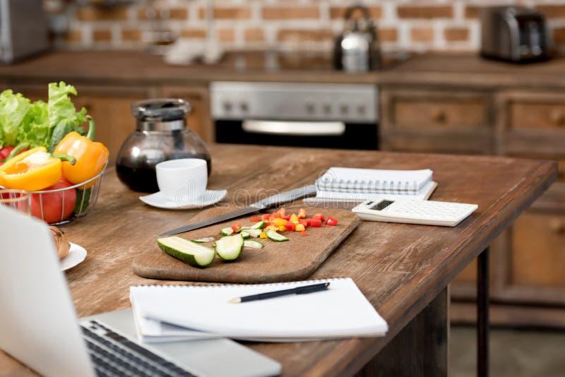 tir en gros plan de lieu de travail de télétravail à la cuisine avec la nourriture sur la table photographie stock libre de droits
