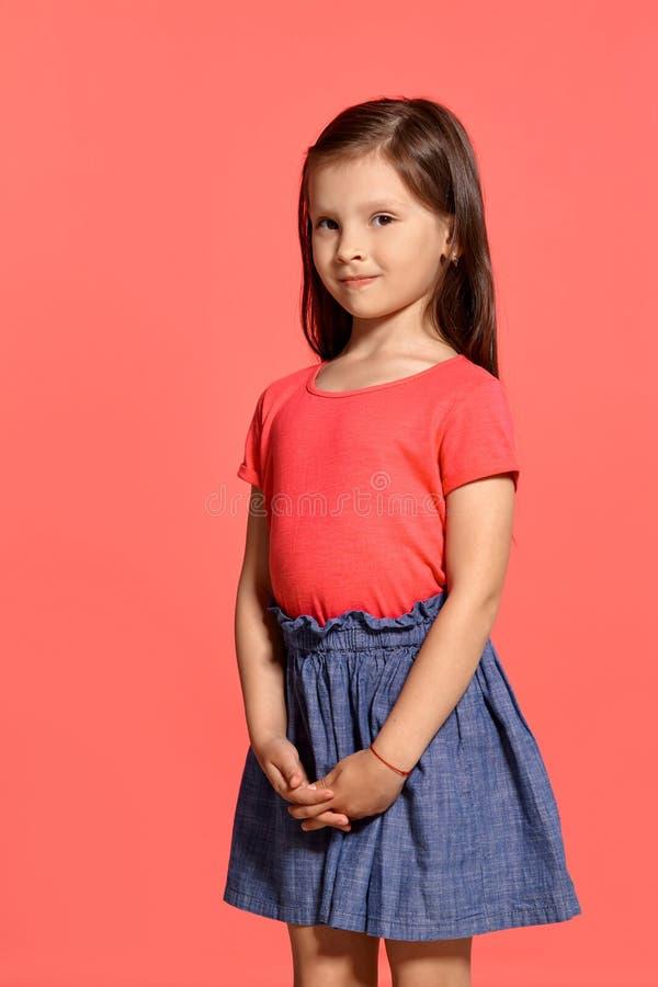 Tir en gros plan de studio de la petite fille de belle brune posant sur un fond bleu image libre de droits