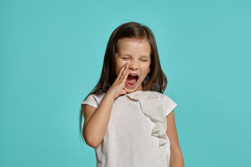 Tir en gros plan de studio de la petite fille de belle brune posant sur un fond bleu images stock