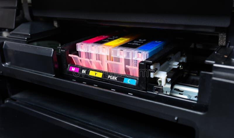 Tir en gros plan des cartouches d'encre de CMYK dans une imprimante couleur images stock