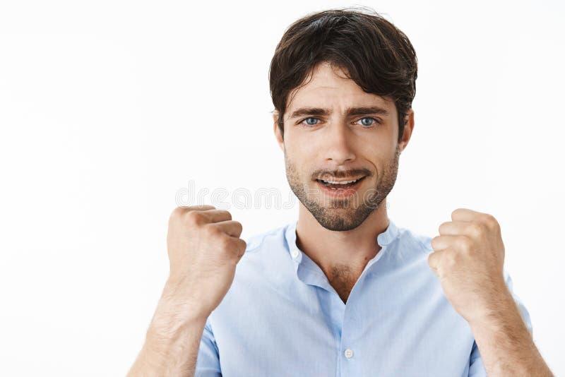 Tir en gros plan jeune d'homme bel créatif sûr et optimiste avec des yeux bleus et de barbe soulevant les poings serrés dans l'ou photos stock