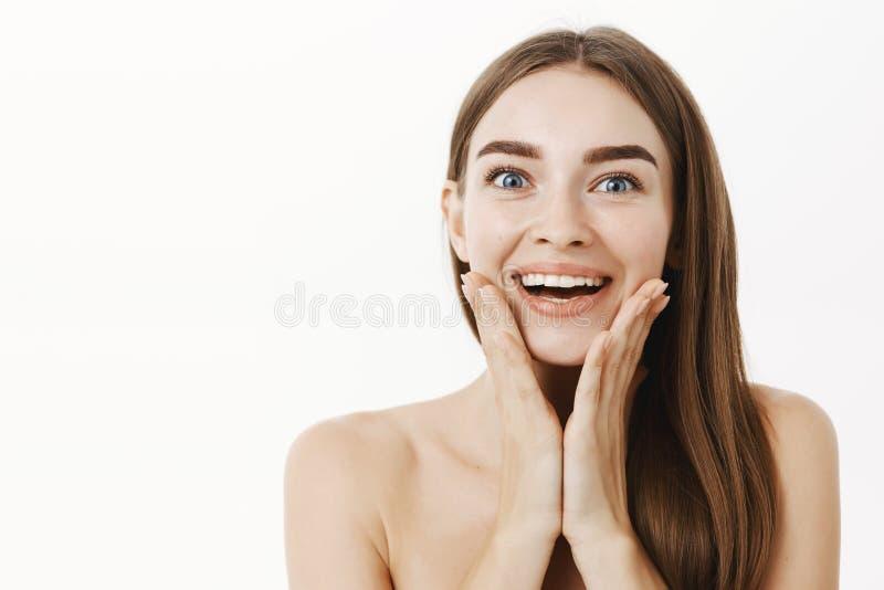Tir en gros plan jeune du visiteur féminin beau impressionné et ravi de station thermale souriant largement tenant des paumes sur images libres de droits