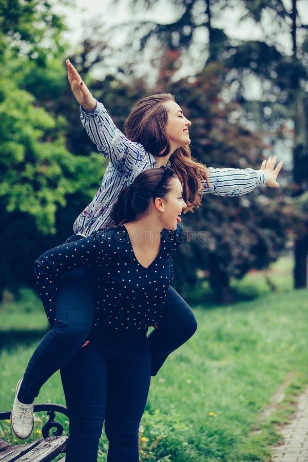 Tir ext?rieur de jeune fille ramenant son ami f?minin sur elle photographie stock libre de droits