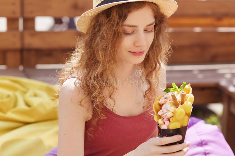 Tir extérieur de la jeune fille mignonne romantique regardant son dessert, étant en optimismes, faim se sentante, tenant la crème photos libres de droits