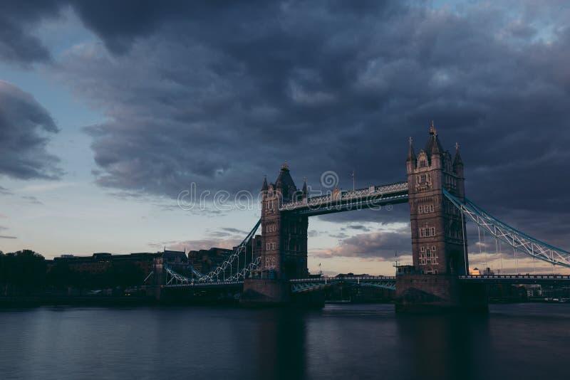 Tir foncé déprimé de pont de tour sur l'horizon de Londres au coucher du soleil photo stock