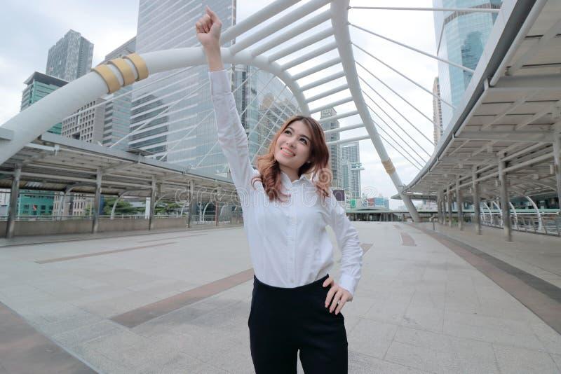 Tir grand-angulaire de la jeune femme asiatique réussie d'affaires soulevant sa main et souriant au fond urbain de bâtiment photographie stock