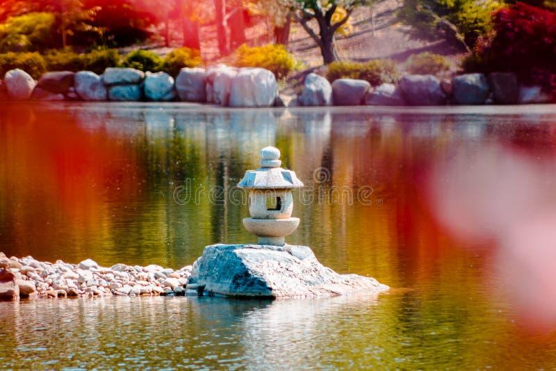 Tir haut étroit d'une statue de lanterne japonaise au milieu d'un étang encadré par les feuilles rouges photo stock