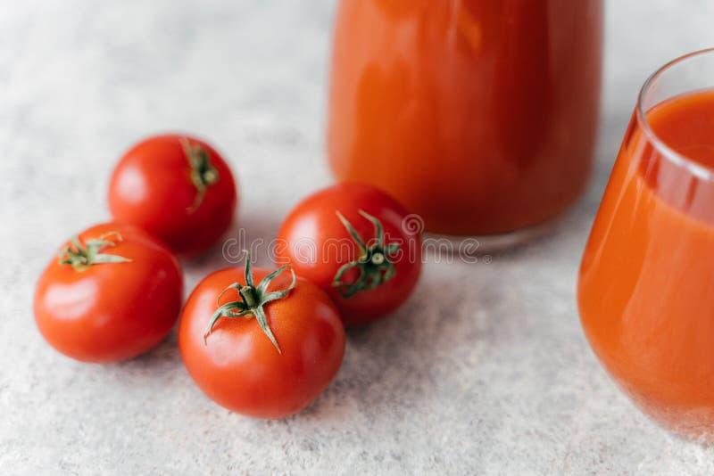 Tir haut ?troit de quatre tomates rouges m?res sur le fond blanc, jus frais en verres pr?s Style de vie sain La boisson d?licieus photo libre de droits