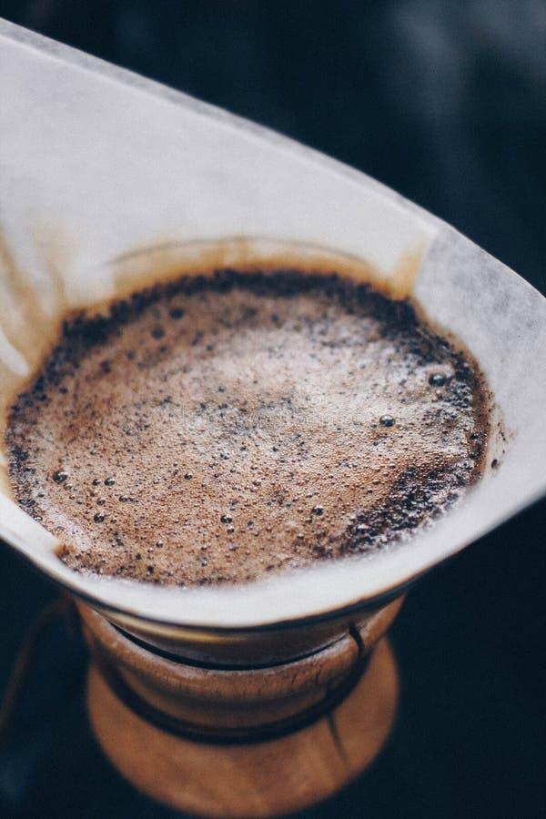 Tir haut étroit du café étant brassé dans un papier filtre dans un petit fabricant de café photos libres de droits