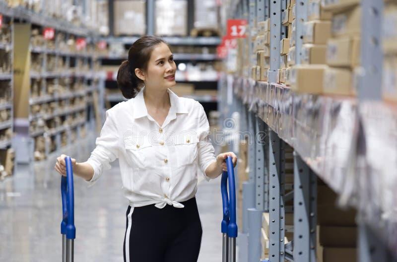 Tir haut ?troit du joli client asiatique recherchant des produits dans l'entrep?t de magasin La fille poussant le chariot et trou photo libre de droits