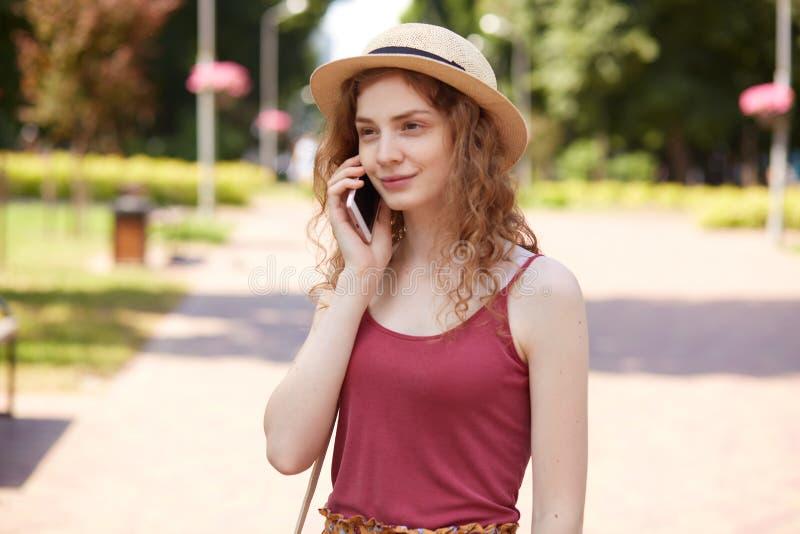 Tir horizontal de belle jeune femme dans le chapeau de paille et le T-shirt de Bourgogne, étant en parc de ville, ayant le repos  photos libres de droits