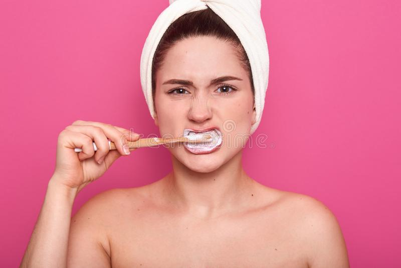 Tir horizontal de jeune femme avec l'expression du visage fâchée, se brossant les dents avec la brosse à dents et la pâte dentifr photo libre de droits