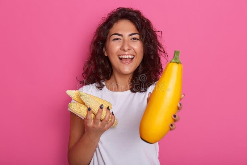 Tir horizontal de la dame attirante gaie regardant directement la caméra avec le sourire toothy, tenant les épis de maïs et la co photographie stock libre de droits