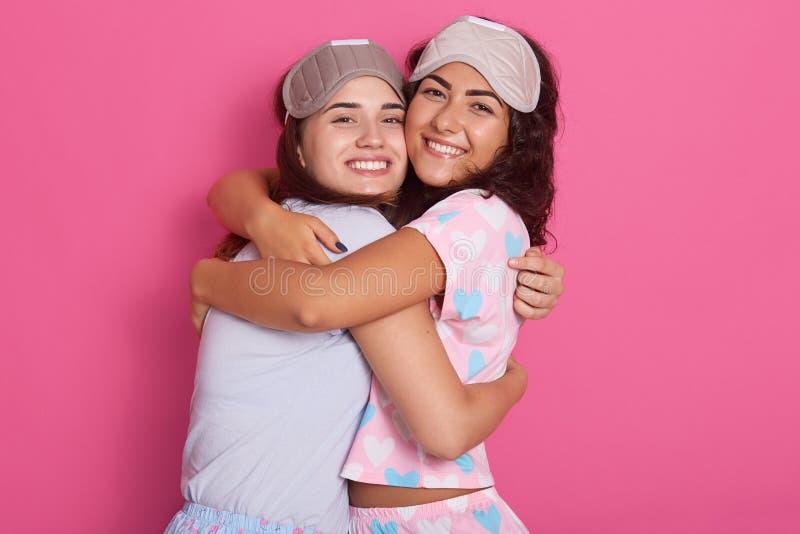Tir horizontal des masques de sommeil et des pyjamas habillés belles par filles, position souriant et étreignant contre le mur ro images stock