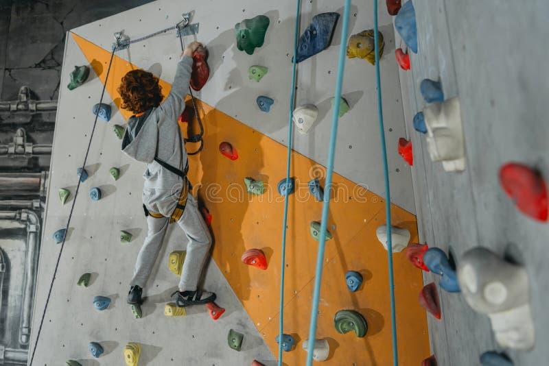 Tir intégral de petit garçon dans un harnais escaladant un mur avec des poignées photos stock