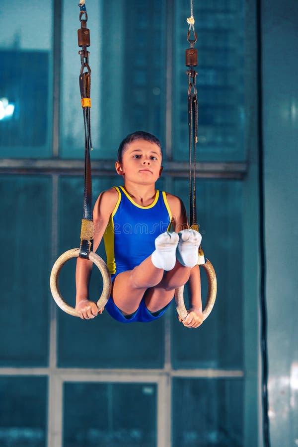 Tir intégral de rearview d'un athlète masculin traction-UPS de exécution sur les anneaux gymnastiques photographie stock libre de droits