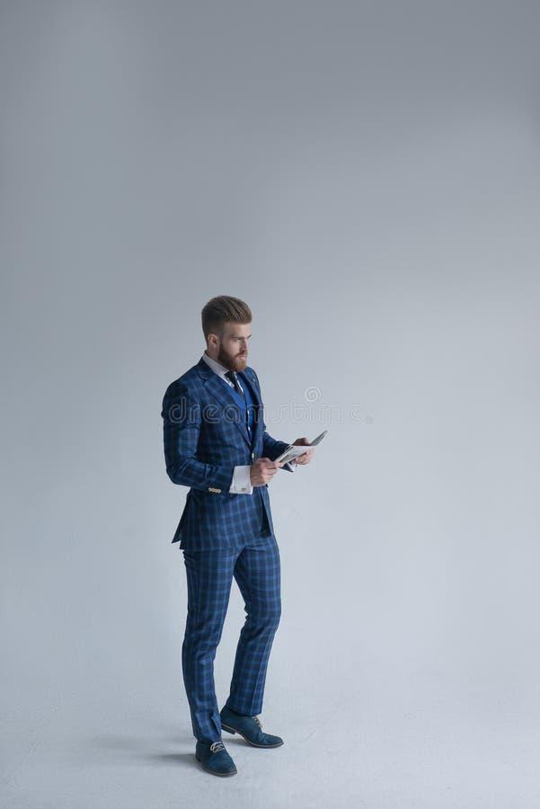 Tir intégral du jeune chef élégant barbu d'homme d'affaires utilisant à l'intérieur le costume en trois pièces avec le journal de photos libres de droits