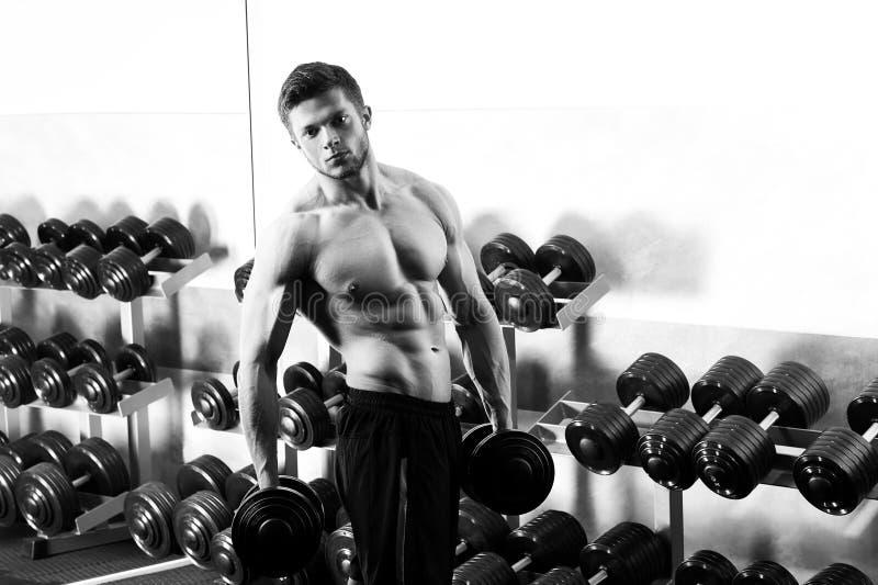 Tir monochrome d'un homme sans chemise déchiré s'exerçant avec le dumbbe photos stock