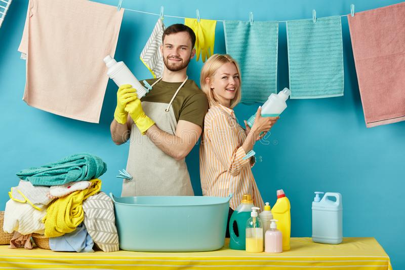 Tir positif de jeune homme et de femme des bouteilles de liquide de lavage image stock