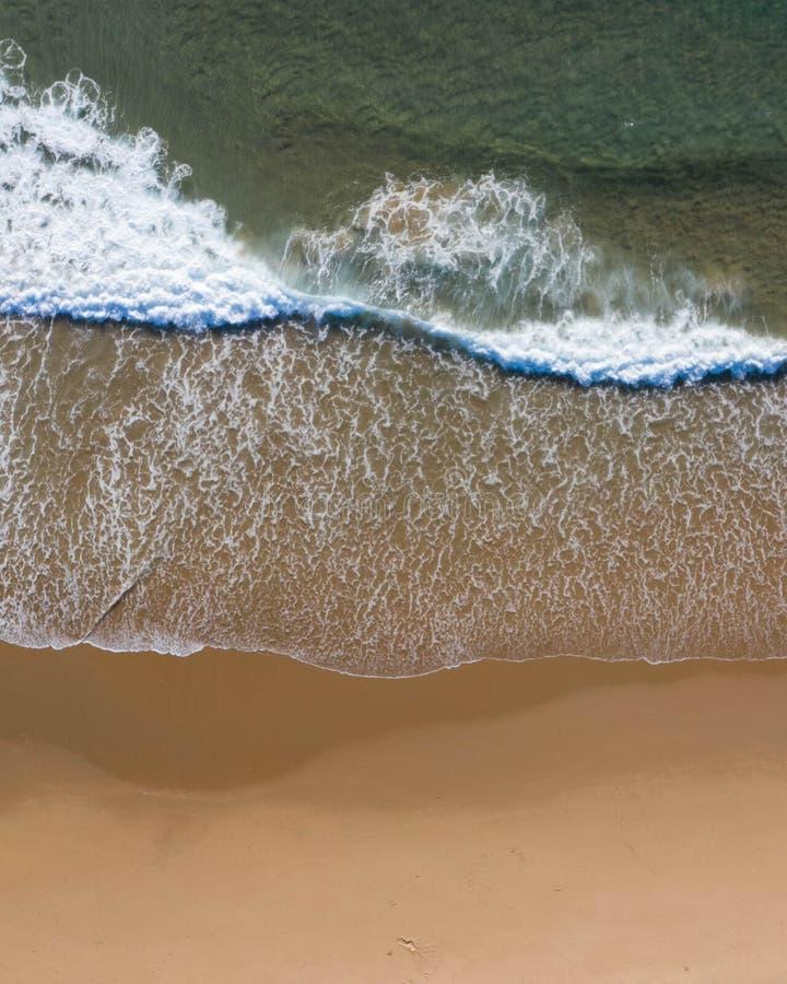 Tir supérieur aérien d'une plage avec le sable gentil, l'eau bleue de turquoise et le vibe tropical photographie stock libre de droits