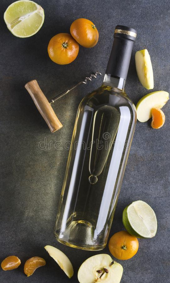 Tir vertical Bouteille de vin blanc, de tire-bouchon et de fruits frais sur la surface grise, vue sup?rieure images libres de droits