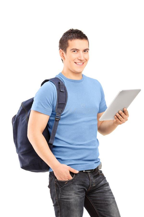 Tir vertical d'un étudiant masculin tenant un comprimé photo libre de droits