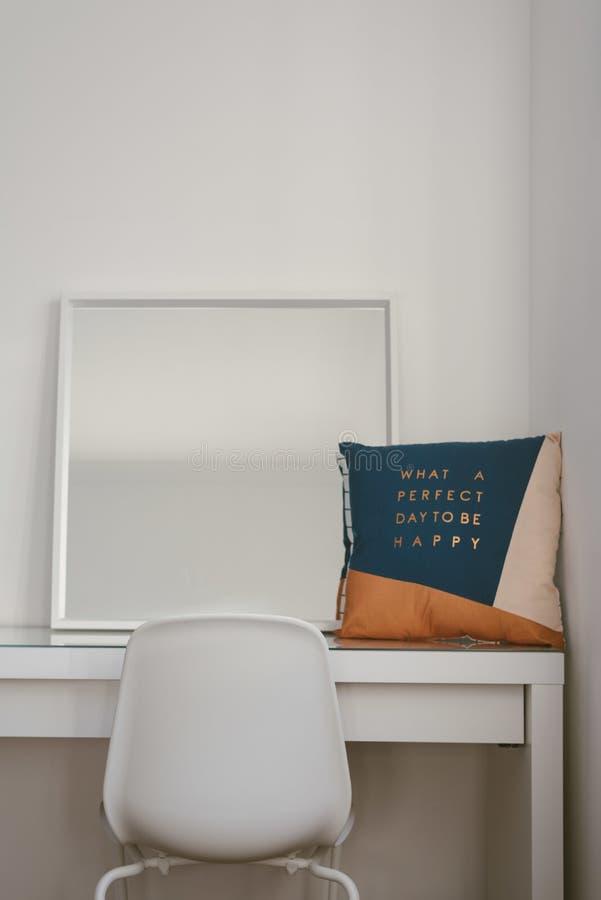 Tir vertical d'un miroir et d'un coussin sur une table blanche avec une chaise dans l'avant photographie stock