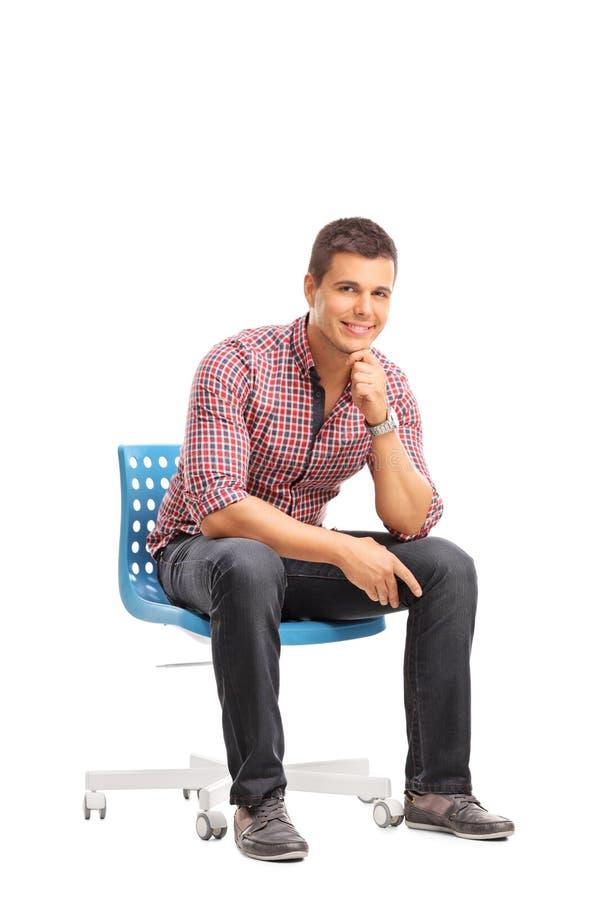 Tir vertical d'un type occasionnel s'asseyant sur une chaise image libre de droits
