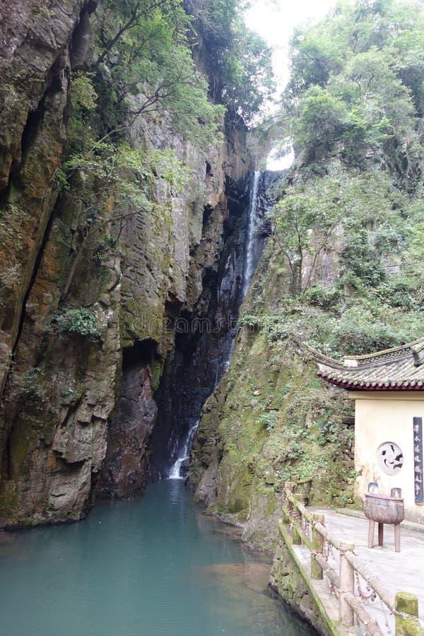 Tir vertical d'une cascade entrant vers le bas dans un étang près d'une maison photographie stock libre de droits