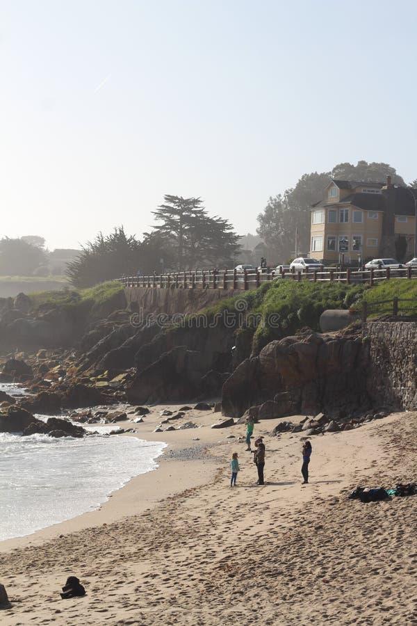Tir vertical d'une position de famille sur le rivage de plage près d'une falaise avec le bâtiment sur le dessus image stock