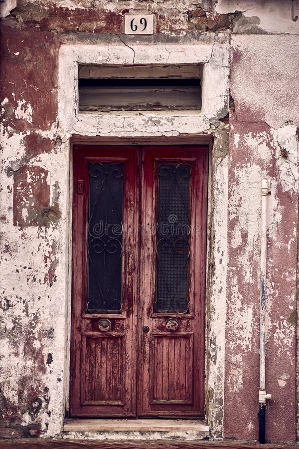 Tir vertical d'une vieille porte superficielle par les agents rouillée en bois d'un bureau abandonné avec les murs sales autour photographie stock