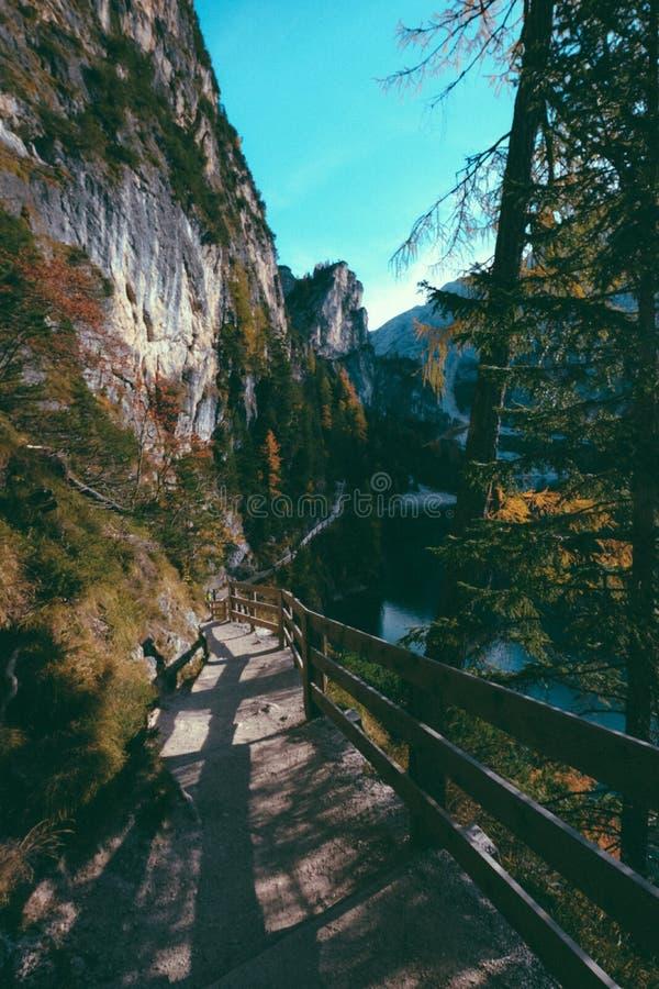 Tir vertical d'une voie avec la barrière en bois du côté d'une montagne un jour ensoleillé image stock