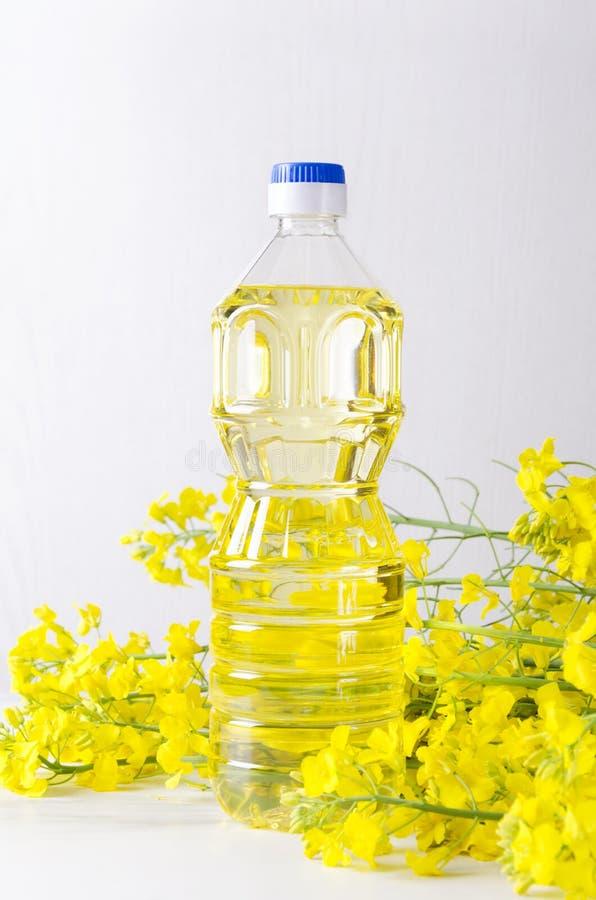 Tir vertical de bouteille d'huile de canola L'huile de graine de colza dans la bouteille en plastique et a sélectionné les fleurs images libres de droits