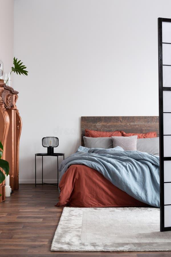 Tir vertical de chambre à coucher industrielle avec les planchers en bois dur, le portail de cuivre de cheminée et le lit en bois photo libre de droits