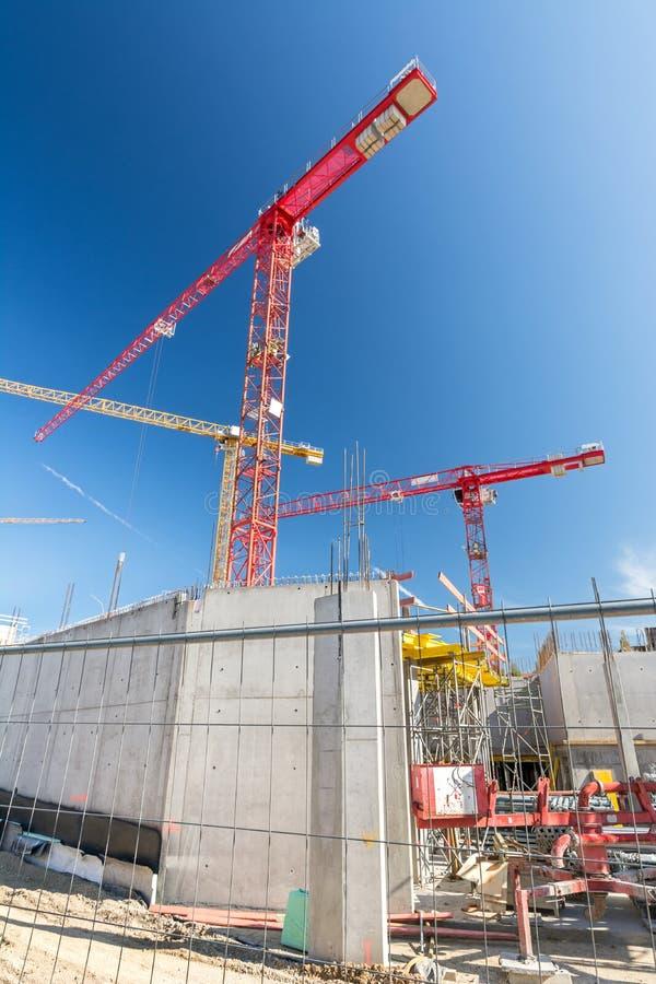 Tir vertical de grand chantier de construction avec la barrière et les grues de construction photographie stock libre de droits