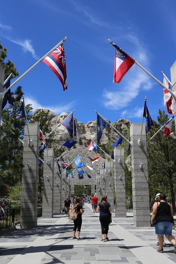 Tir vertical de montagne de marche Rushmore de towerd de personnes sous les drapeaux photographie stock libre de droits
