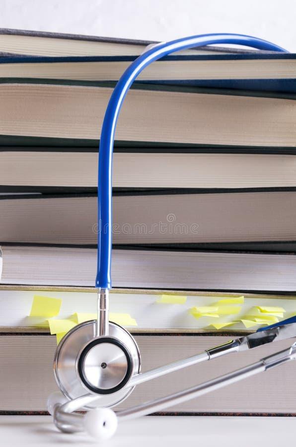 Tir vertical Plan rapproché de pile des livres et du stéthoscope médicaux image libre de droits