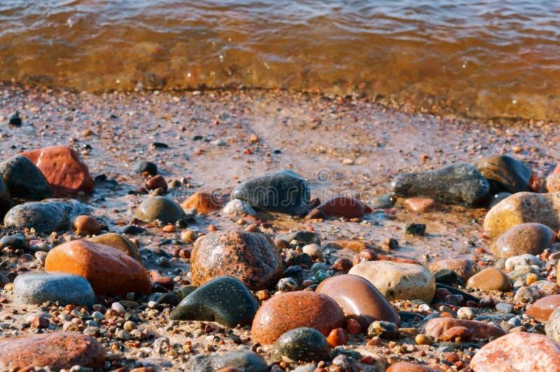 Tira costera, rollos en las piedras, piedras mojadas de la onda del mar foto de archivo libre de regalías