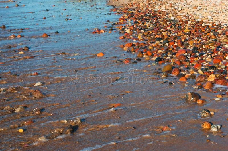 Tira costera, rollos en las piedras, piedras mojadas de la onda del mar imagen de archivo libre de regalías