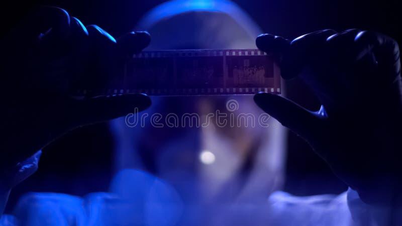 Tira de película de observación del ayudante de laboratorio, buscando pruebas contra criminal imagenes de archivo