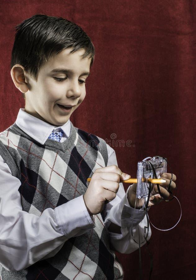 Tira rolada da gaveta com um lápis. Cassete de banda magnética da posse do menino. imagem de stock royalty free