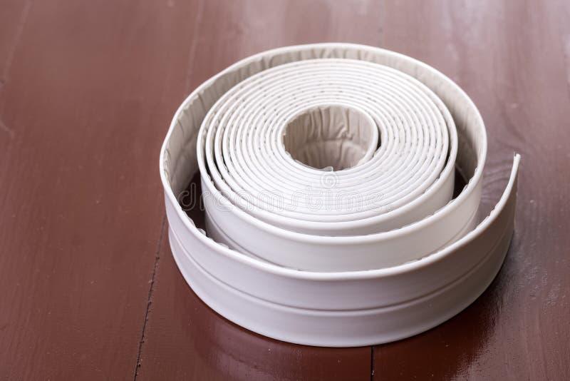 Tira sanitaria blanca del sellante en la tabla marrón de madera foto de archivo libre de regalías