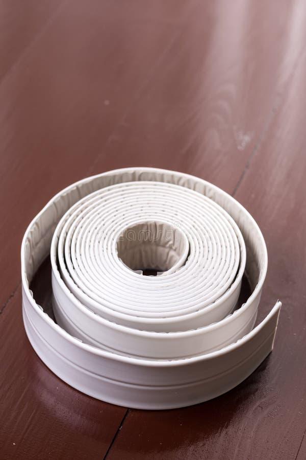 Tira sanitaria blanca del sellante en la tabla marrón de madera imagenes de archivo