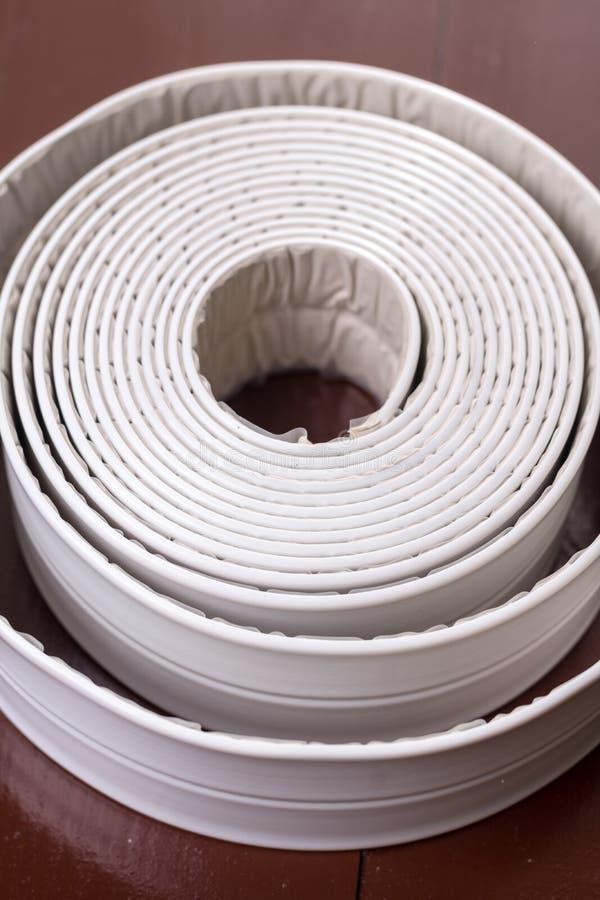 Tira sanitaria blanca del sellante en la tabla marrón de madera fotos de archivo libres de regalías