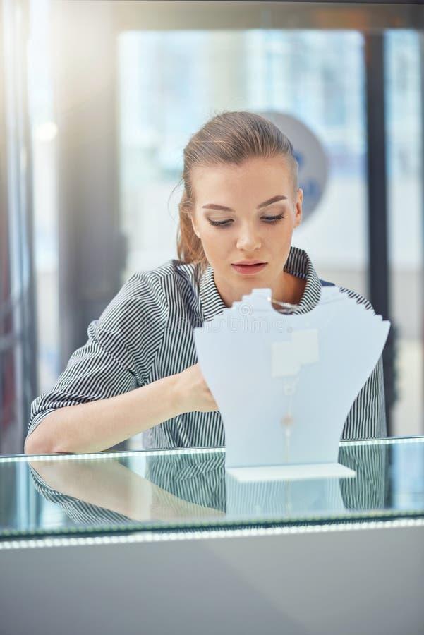 Tirado de la mujer joven atractiva hacia fuera que hace compras para la joyería foto de archivo