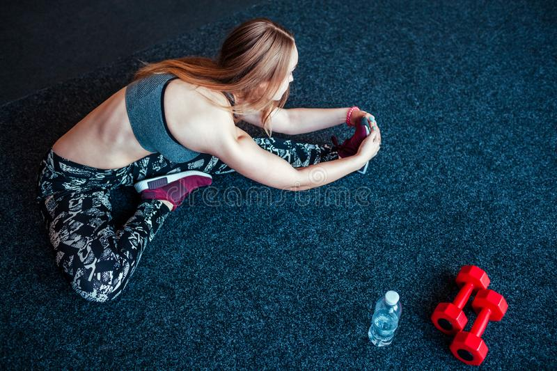 Tirado de la mujer joven que estira en el gimnasio Hembra muscular que hace ejercicios para estirar su cuerpo en el piso imagen de archivo libre de regalías