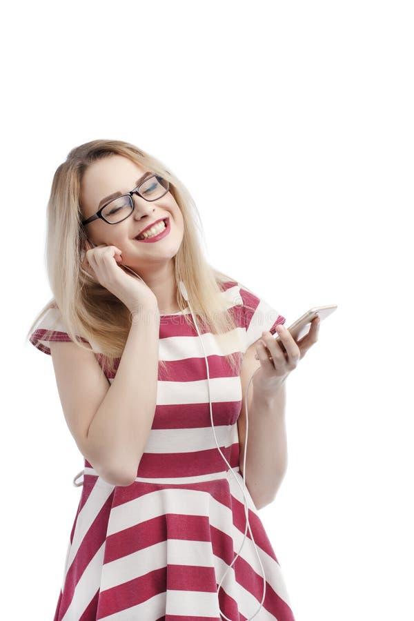 Tirado de muchacha caucásica urbana hermosa con el pelo rubio que sostiene smartphone de moda, música que escucha en los auricula imagenes de archivo