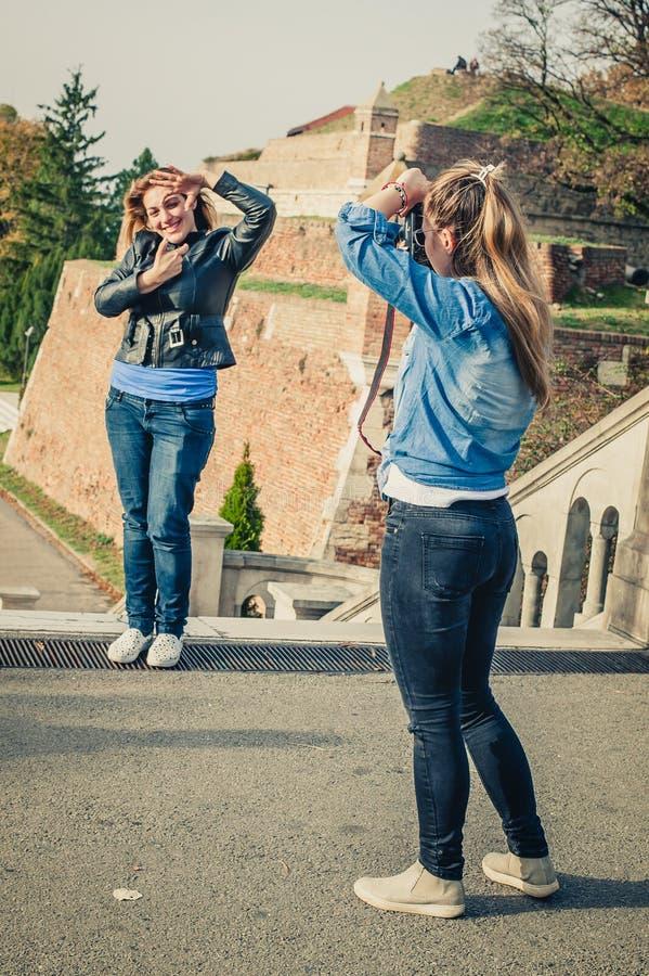 Tirado de un fotógrafo de la muchacha que toma una foto de un su amigo foto de archivo libre de regalías